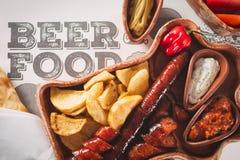 Piwa i przekąski set Rozmaitość piwa, piec na grillu kiełbasy, smażyć grule, solić na drewnianym tle Fotografia Royalty Free