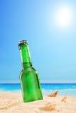 Piwna butelka na piaskowatej plaży z jasnym niebem i słońcem, Obraz Royalty Free