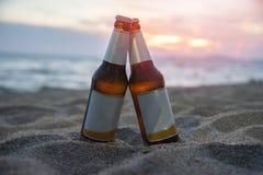 Piwna butelka na piaskowatej plaży z zmierzchu oceanu dennym tłem dla plaży przyjęcia obraz royalty free