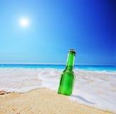 Piwna butelka na piaskowatej plaży z jasnym niebem i fala Zdjęcia Royalty Free