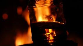 Piwna butelka na pożarniczym tle w zmroku płomień gra na brown szkle 4K zdjęcie wideo