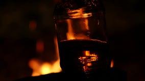 Piwna butelka na pożarniczym tle w zmroku płomień gra na brown szkle swobodny ruch zbiory