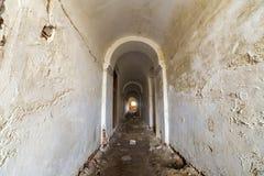 Piwnica stary forteczny budynek, d?ugi w?ski korytarz z przesklepionym gipsuj?cym sufitem i brudna pod?oga, obraz royalty free