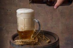 Piwny kubek z pszenicznymi ucho na drewnianej baryłce i ciemnej tło ścianie, nalewa piwo od butelki Fotografia Stock