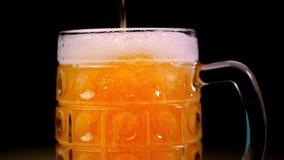 Piwo nalewa w szkło na czarnym tle Piana szybko ono ślizga się przez szkła Pełnego kubka złocisty piwo na a zbiory