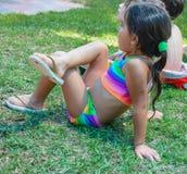 (piwo) Omer, IZRAEL, - dziewczyna siedzi na trawie w lecie w kostiumu kąpielowym i iłołupkach, Lipiec 25, 2015 w Izrael Zdjęcia Stock