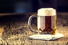 Piwo Szkicu złoty piwo w szklanym słoju Szkicu ale z spienia na wierzchołku Zimny piwo na bardzo starej dąb desce Zdjęcia Stock
