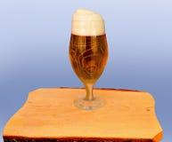 Piwo w szkle na drewnianym stole przeciw zieleni Obrazy Stock