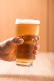 Piwo w szkle, na drewnianym tle Zdjęcia Stock