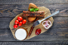 Piwo z kiełbasami, czereśniowymi pomidorami i cebulą, odgórny widok Zdjęcie Stock
