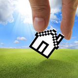 Pixel house icon. Close up of fingers picking up pixel house icon as concept royalty free stock image