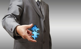 Pixel puzzles icon. Business man hand shows pixel puzzles icon as partnership concept Stock Photos