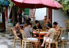 Pixian, China: Shopkeepers Playing Mahjong. Shopkeepers sitting in bamboo chairs sit in front of their stores playing Mahjong on a warm summer afternoon on the Stock Photo