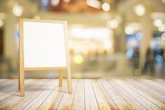Pizarra blanca en blanco del restaurante en piso de madera Fotografía de archivo
