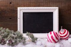 Pizarra, bolas de la Navidad y árbol vacíos de la piel de las ramas en envejecido imágenes de archivo libres de regalías