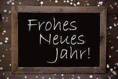 Pizarra con el Año Nuevo malo de Frohes Neues Jahr, copos de nieve Foto de archivo