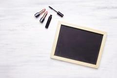 Pizarra con el copyspace, y productos cosméticos en de madera blanco imagen de archivo libre de regalías