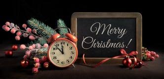 Pizarra con el despertador y decoraciones de la Navidad en negro Foto de archivo libre de regalías