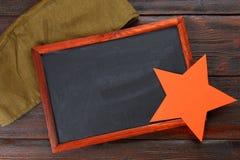 Pizarra con el espacio vacío, el casquillo militar y la estrella roja en una madera Imagen de archivo libre de regalías