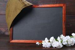Pizarra con el espacio vacío, el casquillo militar y la estrella roja en una madera Foto de archivo