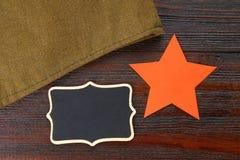 Pizarra con el espacio vacío, el casquillo militar y la estrella roja en una madera Fotos de archivo libres de regalías