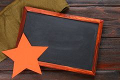 Pizarra con el espacio vacío, el casquillo militar y la estrella roja en una madera Foto de archivo libre de regalías