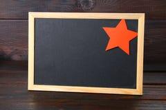 Pizarra con el espacio vacío, el casquillo militar y la estrella roja en una madera Imagenes de archivo