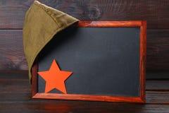 Pizarra con el espacio vacío, el casquillo militar y la estrella roja en una madera Fotografía de archivo