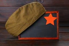 Pizarra con el espacio vacío, el casquillo militar y la estrella roja en una tabla de madera Día del defensor de la patria y del  Imagen de archivo libre de regalías