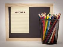 Pizarra con el papel de la libreta y los lápices coloreados Fotos de archivo