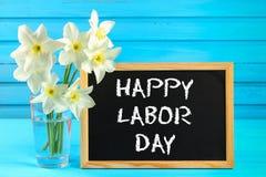 Pizarra con el texto: Día del Trabajo feliz, el 1 de mayo Flores blancas de narcisos en una tabla de madera azul Fotos de archivo libres de regalías