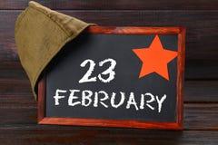 Pizarra con el texto: 23 de febrero Defensor del día de la patria Fotografía de archivo