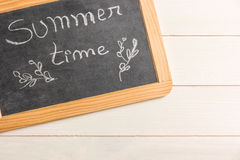 Pizarra con el texto es tiempo de verano en la pizarra de madera Fotografía de archivo libre de regalías