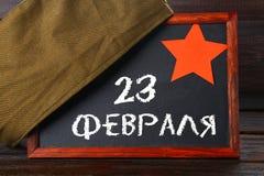 Pizarra con el texto ruso: 23 de febrero El día de fiesta es el día del defensor de la patria Fotos de archivo