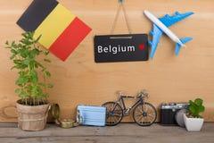 pizarra con el texto y x22; Belgium& x22; , bandera de la Bélgica, modelo del aeroplano, poca bicicleta y maleta, cámara, compás Fotografía de archivo libre de regalías