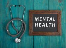 Pizarra con el texto y x22; Health& mental x22; y estetoscopio en fondo de madera azul Foto de archivo