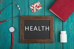 Pizarra con el texto y x22; Health& x22; , píldoras, libro y estetoscopio en fondo de madera Fotos de archivo libres de regalías