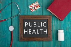 Pizarra con el texto y x22; Health& público x22; , píldoras, libro y estetoscopio en fondo de madera Fotografía de archivo