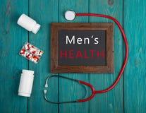 Pizarra con el texto y x22; Men& x27; health& x22 de s; , estetoscopio, píldoras Imagen de archivo