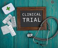 Pizarra con el texto y x22; Trial& clínico x22; , píldoras y estetoscopio en fondo de madera azul imágenes de archivo libres de regalías