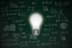 Pizarra con la bombilla que brilla intensamente brillante del concepto de la fórmula y de la idea de la matemáticas foto de archivo libre de regalías