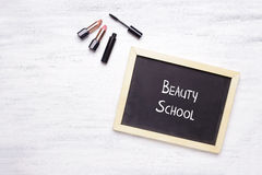 Pizarra con la escuela de la belleza escrita en ella, y produc cosmético imagen de archivo
