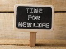 Pizarra con la hora para la nueva palabra del trabajo en fondo de madera Foto de archivo