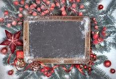 Pizarra con las decoraciones de la Navidad en la nieve, espacio Fotos de archivo
