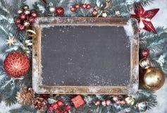 Pizarra con las decoraciones de la Navidad en la nieve, texto Foto de archivo