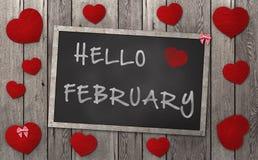 Pizarra con las palabras hola febrero, rodeado por los corazones rojos en fondo de madera resistido Imagen de archivo libre de regalías
