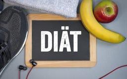 Pizarra con los zapatos, las frutas y la toalla del deporte con la palabra alemana para la dieta imagenes de archivo