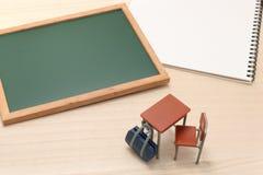 Pizarra, cuaderno, escritorio, y bolso de escuela en la madera Imagen de archivo