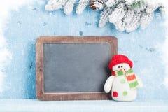 Pizarra de la Navidad, muñeco de nieve y árbol de abeto Imagen de archivo libre de regalías