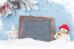 Pizarra de la Navidad, muñeco de nieve y árbol de abeto Fotografía de archivo